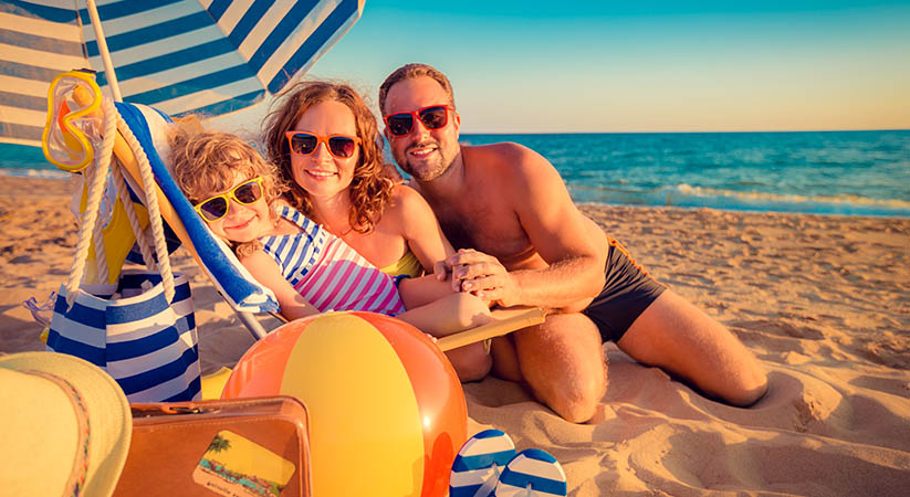 Happy family sitting on the sunbed. Man, woman and child having fun at the beach. Summer vacation concept