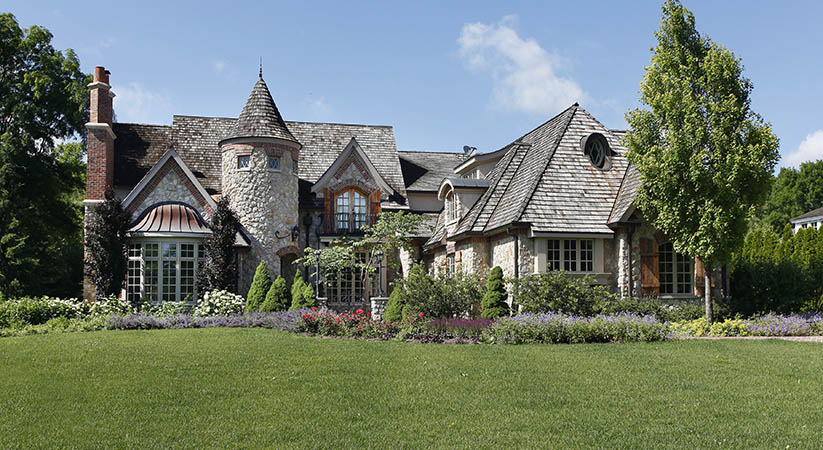 Luxury stone home with turret and cedar roof