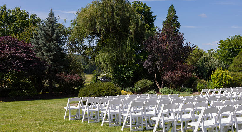 Rows of formal white wooden wedding chairs set up for a wedding or concert
