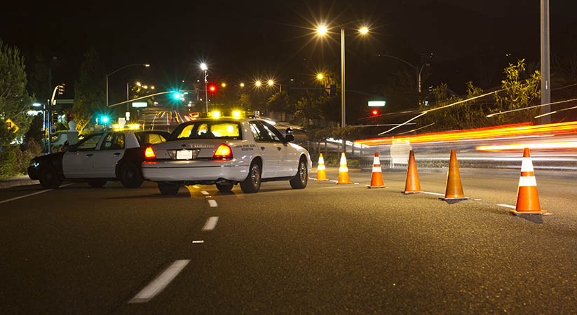 Police vehicles and cones guiding motorists into nighttime sobriety checkpoint, car lights in motion